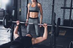 colpo potato del sollevamento pesi dell'uomo mentre donna che sta vicino fotografia stock