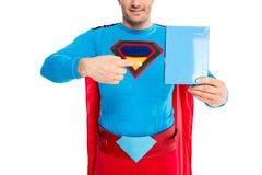 colpo potato del superman sorridente che indica con il dito alla scatola in bianco con il detersivo fotografie stock