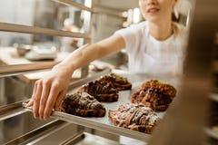 colpo potato del vassoio femminile della tenuta del panettiere di croissant di recente al forno immagine stock libera da diritti