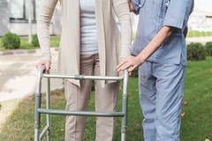 colpo potato dell'infermiere che aiuta paziente senior immagine stock