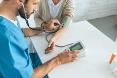 colpo potato dell'infermiere maschio nella pressione sanguigna di misurazione dello stetoscopio a immagine stock libera da diritti
