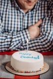 colpo potato dell'uomo che si siede con la torta di compleanno fotografia stock