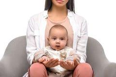 colpo potato della donna che tiene bambino infantile mentre sedendosi sulla sedia del bracciolo fotografia stock