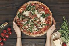 Colpo potato della donna che tiene pizza casalinga con gli ingredienti Fotografia Stock Libera da Diritti