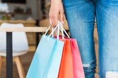 colpo potato della donna con i sacchetti della spesa variopinti a disposizione Fotografia Stock Libera da Diritti
