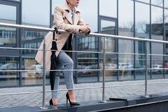 colpo potato della donna di affari nella condizione alla moda del cappotto fotografie stock libere da diritti