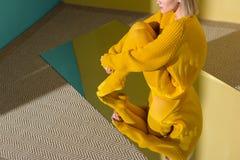 colpo potato della donna in maglione giallo e calzamaglia che si siedono sullo specchio con la riflessione fotografia stock