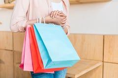 colpo potato della giovane donna con i sacchetti della spesa variopinti Fotografia Stock Libera da Diritti