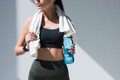 colpo potato della sportiva con la bottiglia della tenuta dell'asciugamano di acqua immagine stock libera da diritti