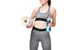 colpo potato della sportiva sorridente che tiene la stuoia di yoga e bottiglia di acqua fotografie stock