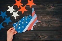 Colpo potato delle stelle e della mano femminile con il pezzo di mappa con la bandiera americana sul ripiano del tavolo di legno Fotografie Stock