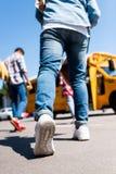 colpo potato dello scolaro che cammina allo scuolabus immagine stock libera da diritti