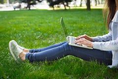 Colpo potato di giovane donna castana su un'erba, lavorante con il computer portatile nel parco Fotografia Stock