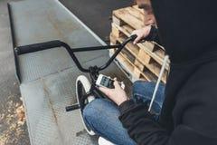 colpo potato di giovane motociclista del bmx che per mezzo dello smartphone fotografia stock libera da diritti