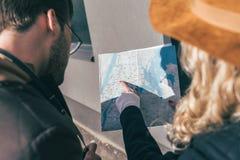 colpo potato di giovani coppie che indicano alla mappa mentre stando insieme fotografie stock