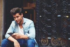 Colpo potato di un uomo alla moda che utilizza il suo telefono cellulare nell'ambiente urbano Fotografia Stock Libera da Diritti