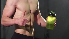 Colpo potato di un uomo senza camicia con acqua perfetta della tenuta dell'ABS che mostra i pollici su fotografie stock