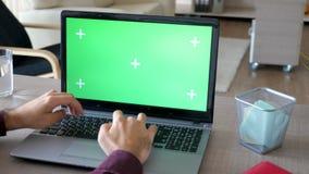 Colpo rivelante dell'uomo d'affari a casa che scrive e che lavora ad un computer portatile con derisione verde dello schermo su archivi video