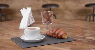Colpo rivelante di una tazza fresca di coffe nero con un croissant delizioso stock footage