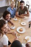 Colpo sopraelevato degli amici che si incontrano per il pranzo in caffetteria fotografia stock