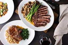 Colpo sopraelevato di una tavola di cena con bistecca e carne di maiale arrostita immagini stock