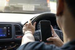 Colpo sopraelevato un uomo che per mezzo del telefono cellulare mentre conducendo un'automobile, modo fotografie stock