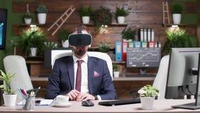 Colpo statico dell'impiegato di concetto con una cuffia avricolare di realtà virtuale di VR video d archivio