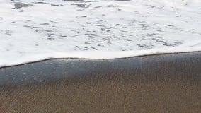 Colpo stretto delle onde di oceano spumose sulla spiaggia di sabbia archivi video