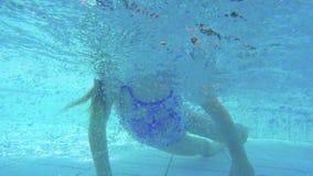 Colpo subacqueo della bambina che si tuffa una piscina stock footage