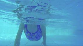 Colpo subacqueo della bambina che si tuffa una piscina archivi video