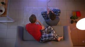 Colpo superiore del tipo in indumenti da notte che giocano videogioco ed altro che si rilassa sul sofà nel salone stock footage