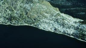 Colpo superiore dell'antenna 4k del lago fra la montagna dell'abetaia della neve nel paesaggio di inverno stock footage