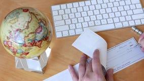 Colpo superiore dell'uomo di bsiness che scrive un assegno con la filatura del globo stock footage