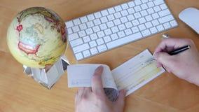 Colpo superiore dell'uomo di bsiness che scrive un assegno con la filatura del globo archivi video