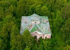 Colpo superiore di vista aerea di costruzione abbandonata nella foresta verde densa invalicabile immagini stock