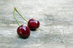 Colpo superiore, fine su della ciliegia fresca con le gocce di acqua sul fondo di legno rustico leggero della tavola, fuoco selet fotografia stock