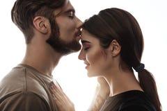 Colpo tenero dell'uomo bello che bacia donna alla fronte Fotografie Stock Libere da Diritti