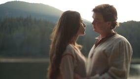Colpo tenero di belle coppie nell'amore in vestiti ucraini tradizionali che abbracciano morbidamente sul pilastro sul lago della  stock footage