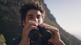 Colpo tenuto in mano del primo piano della viandante che guarda tramite il binocolo stock footage