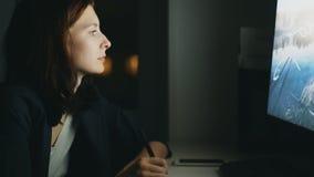 Colpo tenuto in mano del primo piano del progettista concentrato della donna che lavora nell'ufficio alla notte facendo uso del c video d archivio