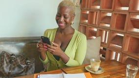 Colpo tenuto in mano della donna afroamericana nera attraente e felice di affari che lavora online con il telefono cellulare che