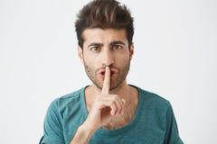 Colpo in testa del maschio caucasico alla moda attraente in maglietta blu casuale, tenendo il dito indice alle labbra, chiedenti  Immagini Stock Libere da Diritti