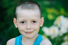 Colpo in testa del ragazzo felice di sorriso che porta camicia blu isolata su natur Immagini Stock Libere da Diritti