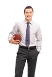 Colpo verticale di giovane uomo d'affari che tiene un calcio Fotografia Stock