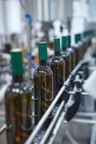 Colpo verticale di una fila delle bottiglie di vino di vetro che si muovono dal trasportatore immagine stock