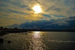 Colred and dark sunrise clouds over the Cantabrian Sea in Gijon stock image
