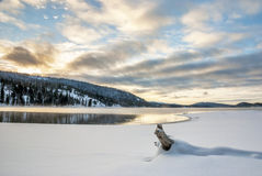 Colroful sunrise sky over a snow lined lake stock images