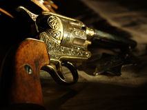 Colt 45 Peacemaker. Detail photo of a Peacemaker resting on a leather holster with a badge in the background Stock Images