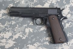 Colt government M1911 on US ARMY uniform. Background royalty free stock photo