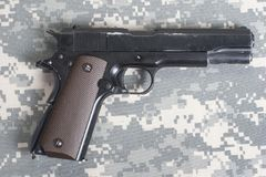 Colt government M1911 on US ARMY uniform. Background royalty free stock image